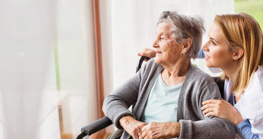 caregiver and senior woman looking outside the window