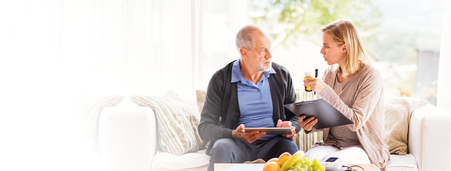 caregiver giving reminder to senior man