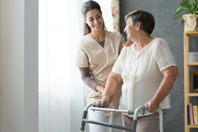 caregiver and senior woman with walker at home